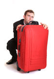 Distrustful business man behind red luggage Royalty Free Stock Photography