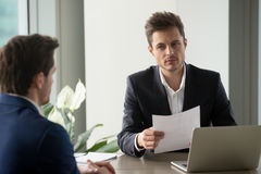 Distrustful businessman holding document, reading bad resume at. Distrustful businessman holding document at meeting, looking at partner with doubt suspicion stock image