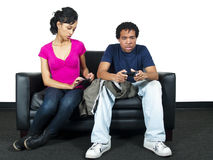Distrusting girlfriend. Is snooping on guy's text messages while he is busy playing video games stock photos