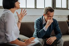 Disturb and upset old man crying and being depressed. Thoughts and feelings. Disturbed and upset old men crying and being depressed while dark-haired doctor stock images