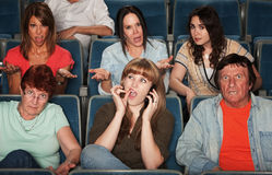 Disturbed Audience. Frustrated audience with rude women on phone Stock Image
