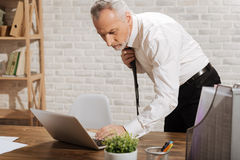 Disturbed entrepreneur reading an email. Bad news. Upset serious nervous businessman looking at the screen of his computer and hitting some buttons while fixing Stock Photo