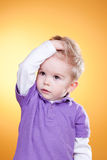 Disturbed little boy hold head with hand Royalty Free Stock Image