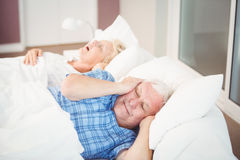 Disturbed man covering ears from snoring wife Royalty Free Stock Image