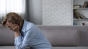 Disturbed senior lady sitting on sofa and crying, bad news, suffering headache royalty free stock photography