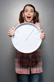 Disturbed woman holding wall clock Royalty Free Stock Images