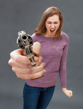 Disturbed young woman with gun screaming expressing frustration and violence. Disturbed young woman holding an oversized hand gun in the foreground, screaming Royalty Free Stock Photo