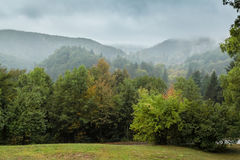 Disturbing landscape with grassed outskirts, forest thicket and. Foggy mountains in the distance in rainy day with grey cloudy stormy sky in Plitvice Lakes Royalty Free Stock Photos