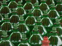 Disturbing. Many green plastic bottles only one red Stock Photos