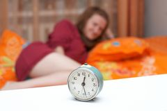 Disturbing a sleeping woman. Alarm clock disturbing a sleeping woman that is defocused Royalty Free Stock Photos