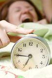 Disturbing a sleeping woman. Alarm clock disturbing a sleeping woman that is defocused Royalty Free Stock Images