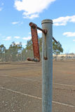 Disused asphalt tennis court and rusty net post. Disused asphalt tennis court and rusty tennis net post Royalty Free Stock Images