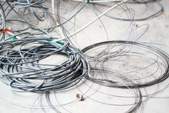 Disused discarded ruined abandoned LAN cable wires roll circle rope on the floor renovation decoration refurbish garbage trash. Roll the circle rope,Electric royalty free stock photo