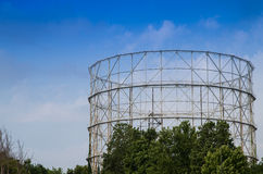 Disused gasometer metal covered with vegetation Stock Photos