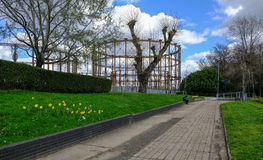 Disused gasworks in East London from pathway. Disused gasworks in East London from pathway near River Lea.  Shows a man sitting on the wall.  A springtime shot Royalty Free Stock Photos