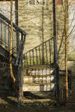 Disused metal steps. Disused metal fire escape steps to the rear of a derelict building casting shadows on the stone wall, with tress and shrubs growing around Stock Photography