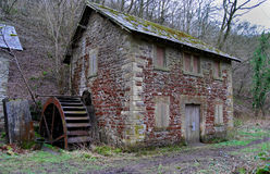 Disused Mill with Water Wheel. A boarded up disused mill with water wheel Stock Photos