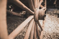 Disused old cart wheel closeup. Retro vintage sepia image of a disused old wooden cart wheel Stock Image