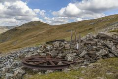 Disused pit head wheels. A pair of disused pit head wheels lie on the ground next to an old shaft on the side of Moelwyn Mawr. The shaft sits above Croesor Slate Stock Image