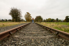 Disused rail track overgrown. Disused railtrack with leaves on the track man on tracks Royalty Free Stock Image