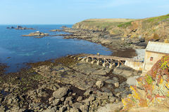 Disused RNLI lifeboat house on The Lizard peninsula Cornwall England UK south of Helston in summer on calm blue sea sky day Stock Image