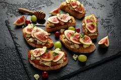 Dit Fig. en Gorgonzola-tartines, toost, bruschetta Gemotregend met honing royalty-vrije stock foto