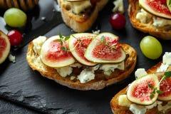 Dit Fig. en Gorgonzola-tartines, toost, bruschetta Gemotregend met honing royalty-vrije stock afbeeldingen