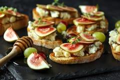 Dit Fig. en Gorgonzola-tartines, toost, bruschetta Gemotregend met honing stock fotografie