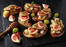 Dit Fig. en Gorgonzola-tartines, toost, bruschetta Gemotregend met honing stock afbeeldingen