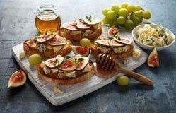 Dit Fig. en Gorgonzola-tartines, toost, bruschetta gemotregend met honing op witte houten raad royalty-vrije stock afbeelding