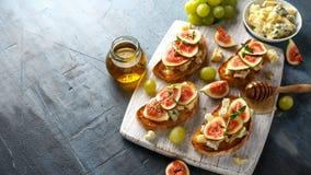 Dit Fig. en Gorgonzola-tartines, toost, bruschetta gemotregend met honing op witte houten raad stock foto