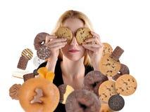 Diät-Frau, die vom Snack-Food auf Weiß sich versteckt Lizenzfreie Stockfotos