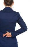 Dita attraversate tenuta della donna di affari dietro indietro. retrovisione Immagini Stock Libere da Diritti