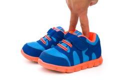Dita che mettono in un paio delle scarpe sportive blu per il bambino Fotografie Stock Libere da Diritti