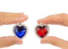 Dita che tengono i cuori blu e rossi dei gioielli Immagine Stock