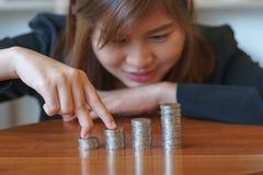 Dita della donna di affari che camminano sulle monete con lo scrittorio di legno immagini stock