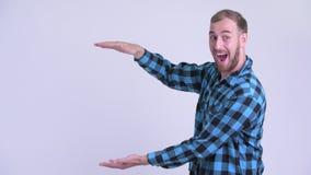 Dita di schiocco dell'uomo barbuto felice dei pantaloni a vita bassa e guardare sorpreso stock footage