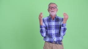 Dita di schiocco dell'uomo barbuto senior felice dei pantaloni a vita bassa e guardare sorpreso video d archivio