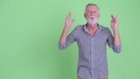 Dita di schiocco dell'uomo barbuto senior felice e guardare sorpreso stock footage