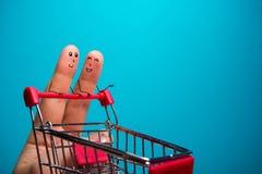 Dita divertenti che comperano al supermercato con il carrello rosso del carretto su fondo blu Immagine Stock