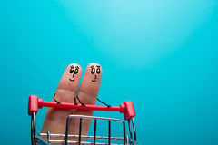 Dita divertenti che comperano al supermercato con il carrello rosso del carretto su fondo blu Fotografia Stock Libera da Diritti