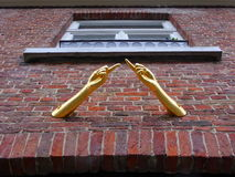 Dita indicanti dorate sulla casa Fotografia Stock