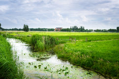 Ditch along a Field in the Countryside of the Netherlands. Rural Landscape with a Ditch in Foreground in the Countryside of The Netherlands on a Cloudy Spring stock photography