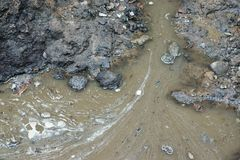 Ditch with dirty water. Fragment of a construction ditch in the earth with dirty sewage Royalty Free Stock Photos