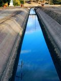 Ditch in the park water canal in the park with sky reflection in the Arizona desert. USA Royalty Free Stock Image