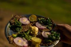 Dites l'arrosage et la nourriture du bout des l?vres authentique de Himachali au-dessus du fond blured de montagne photo stock