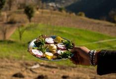Dites l'arrosage et la nourriture du bout des l?vres authentique de Himachali au-dessus du fond blured de montagne photographie stock libre de droits