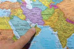 Dito che indica una mappa variopinta del paese degli Emirati Arabi Uniti Dubai in Medio Oriente sul golfo fotografia stock libera da diritti