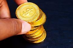 Dito con la moneta di oro Fotografia Stock
