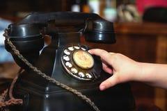 Dito del bambino che gira un vecchio telefono d'annata nero Immagine Stock Libera da Diritti
